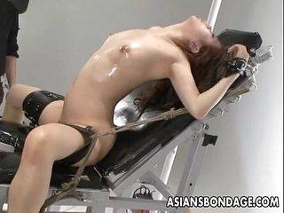 Nasty Asian slut in bondage gets her muff teased